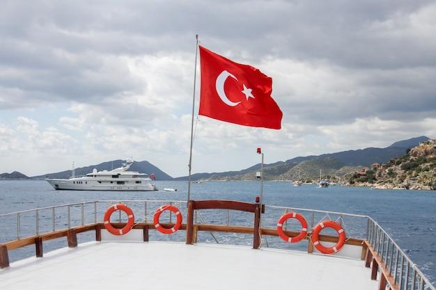 Vlag van turkije op een schip op zee in de buurt van bergen en een luxejacht