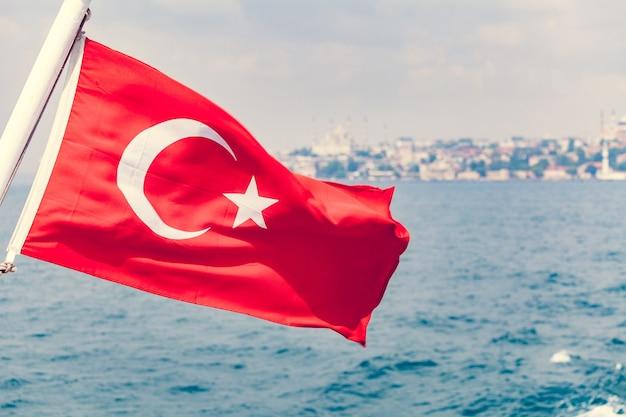 Vlag van turkije zwaaien over blauwe lucht en zee achtergrond