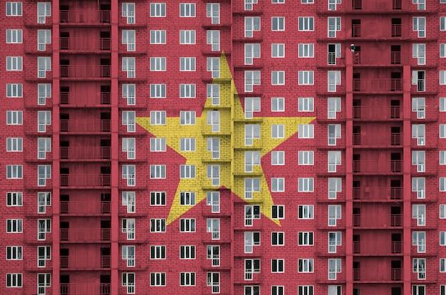 Vlag van vietnam afgebeeld in verfkleuren op woongebouw met meerdere verdiepingen in aanbouw.