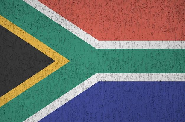 Vlag van zuid-afrika afgebeeld in heldere verfkleuren op oude reliëf pleistermuur.