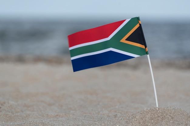 Vlag van zuid-afrika op de achtergrond van de zee. vakantie op het strand in zuid-afrika.
