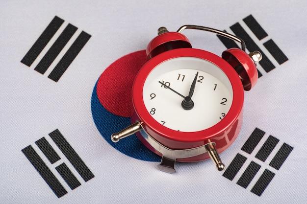 Vlag van zuid-korea en vintage wekker close-up. tijd om te reizen