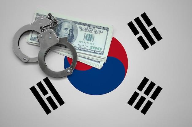 Vlag van zuid-korea met handboeien en een bundel dollars. het concept van het overtreden van de wet en dieven misdaden