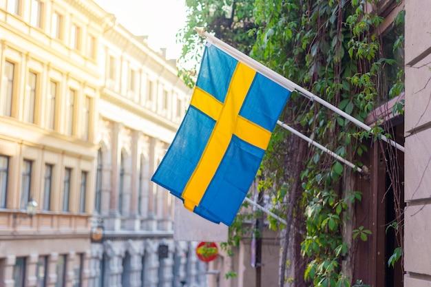 Vlag van zweden op een straat, verlicht door de zon. zweedse vlagkleuren: geel en blauw