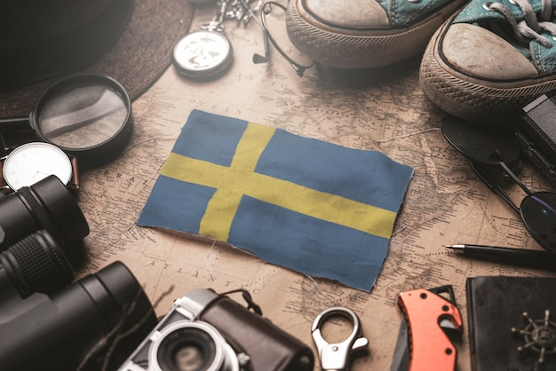 Vlag van zweden tussen de accessoires van de reiziger op oude vintage kaart. toeristische bestemming concept.