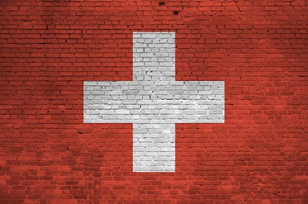 Vlag van zwitserland op oude bakstenen muur