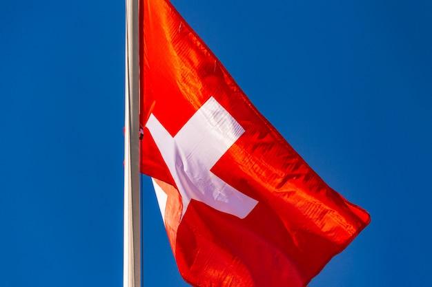 Vlag van zwitserland vliegen in de wind tegen de blauwe hemel