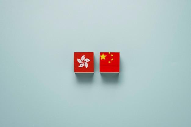 Vlaggen van china en hongkong drukken het scherm af op houten kubusblokken. hongkong en china politiek conflict en protestconcept.