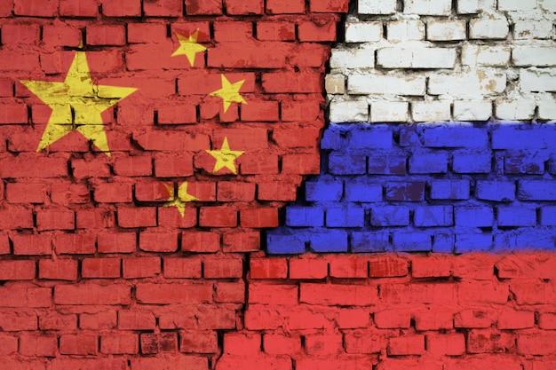 Vlaggen van china en rusland op de bakstenen muur met grote barst in het midden