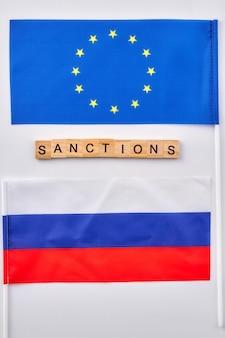 Vlaggen van de russische en europese unie. woordsancties gemaakt van houten kubussen.