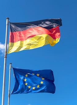 Vlaggen van duitsland en de europese unie tegen blauwe hemel in berlijn