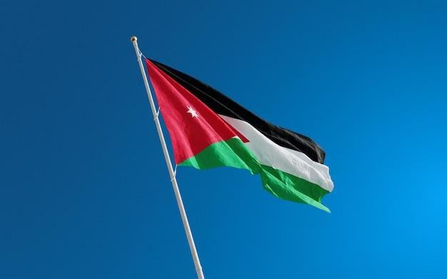 Vlaggen van jordanië geïsoleerd close-up op blauwe achtergrond