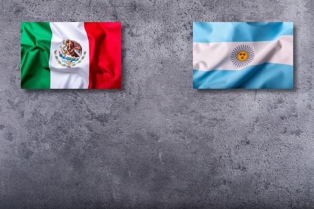 Vlaggen van mexico en argentinië op concrete achtergrond.