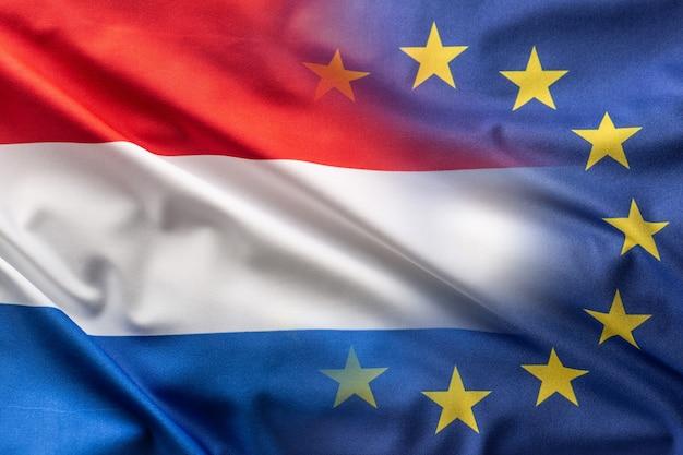 Vlaggen van nederland en de eu die in de wind waaien.