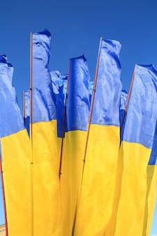 Vlaggen van oekraïne die in de wind tegen diepe blauwe hemel golven.
