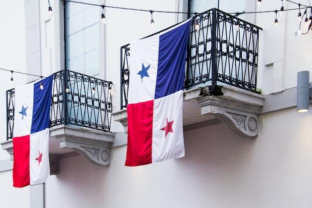 Vlaggen van panama hangen overdag aan de balkons van de huizen in het zonlicht Gratis Foto