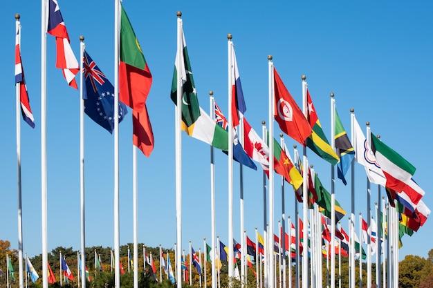Vlaggen van vele staten wapperen op vlaggenmasten.