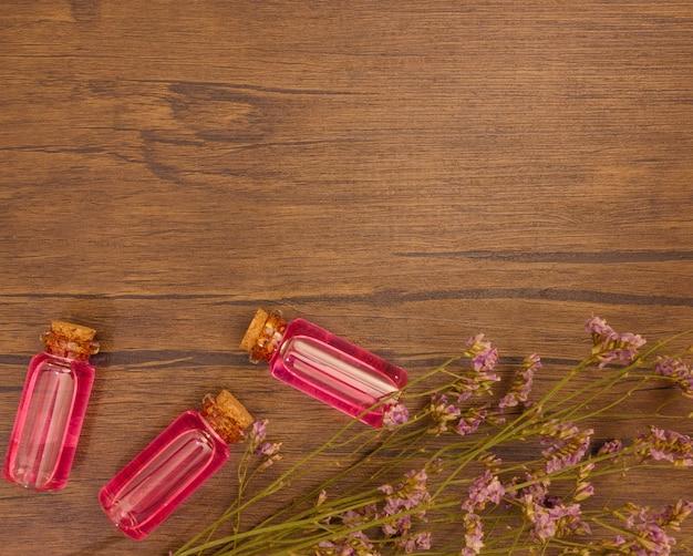 Vlak leg etherische oliën met bloemextract op houten achtergrond met exemplaarruimte