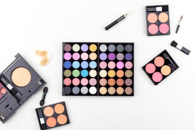 Vlak leg foto van diverse make-upborstel, oogschaduw en schoonheidsmiddelen op witte achtergrond