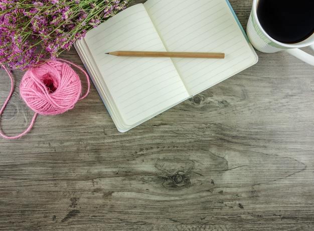 Vlak leg, hoogste menings grijs houten bureau met kantoorbehoeften met inbegrip van notitieboekje en potlood met een kop van koffie