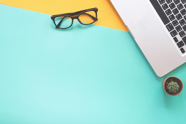 Vlak leg ontwerp van bureau met notitieboekje, oogglazen en cactus op groene en gele achtergrond.