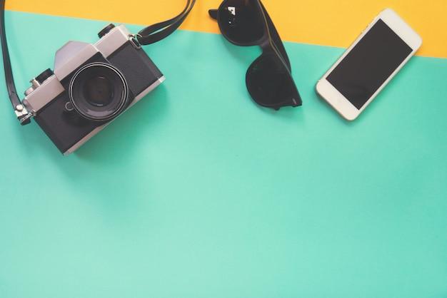 Vlak leg ontwerp van het werkbureau met zonnebril oude camera en smartphone op groene en gele achtergrond.