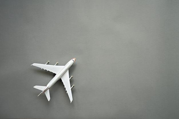 Vlak leg ontwerp van reisconcept met vliegtuig op grijze achtergrond met exemplaarruimte.