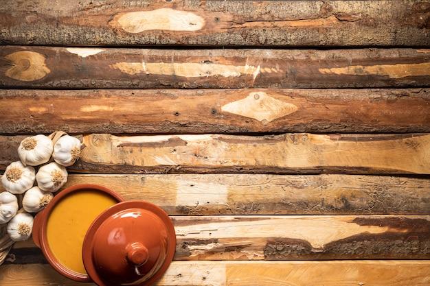 Vlak leg pompoensoep en knoflook op houten achtergrond