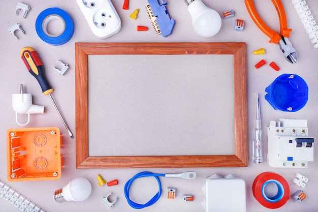 Vlak leg samenstelling met elektricien` s hulpmiddelen, materiaal en ruimte voor tekst op grijze oppervlakte. home reparatie concept.