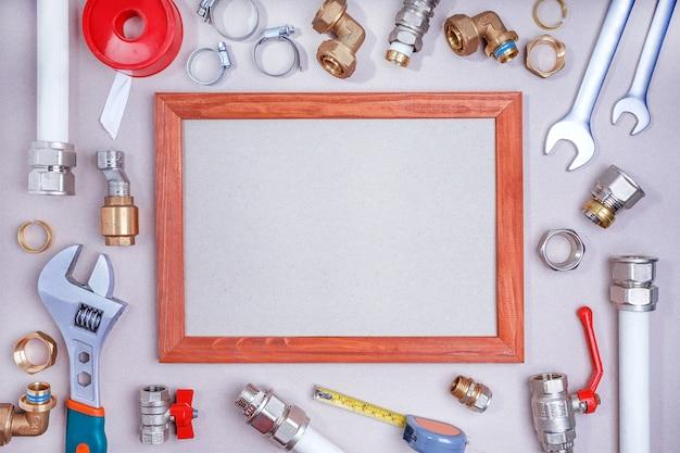 Vlak leg samenstelling met loodgieter` s hulpmiddelen op grijze achtergrond en ruimte voor tekst.