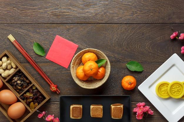Vlak leg sinaasappel en dessert ook rood zakgeld op modern bruin houten thuis bureau.