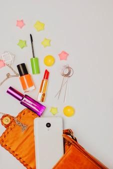 Vlak leg van de oranje zak van de leervrouw opent met schoonheidsmiddelen