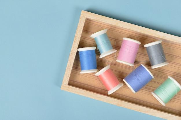 Vlak leg van gekleurde draadbroodjes voor het naaien op blauwe achtergrond