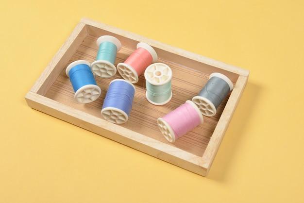 Vlak leg van gekleurde draadbroodjes voor het naaien op gele achtergrond