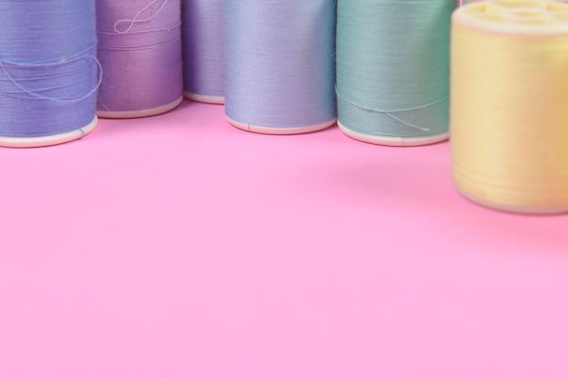 Vlak leg van gekleurde draadbroodjes voor het naaien op roze achtergrond