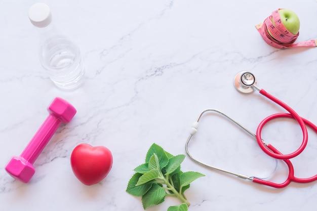 Vlak leg van goed gezond concept, roze domoor met rood hart en stethoscoop en groene appel