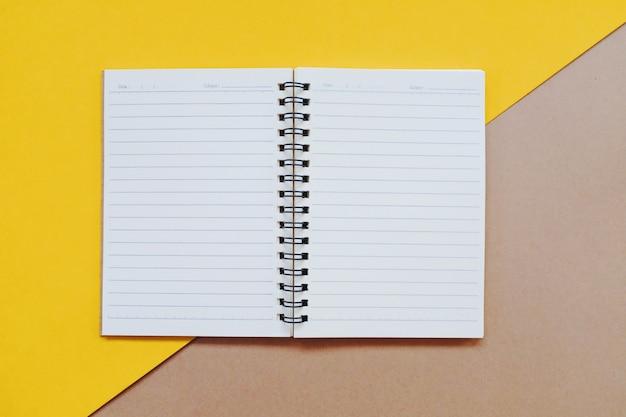 Vlak leg van minimaal werkruimtebureau met notitieboekje op kleurenachtergrond, exemplaarruimte.