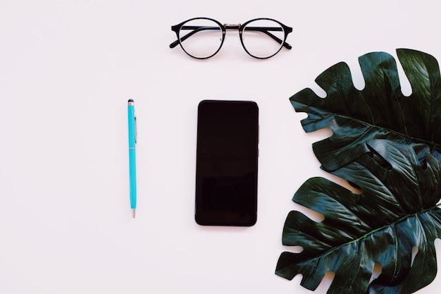 Vlak leg van minimale werkruimtebureau met notitieboekje, oogglazen en groene installatie