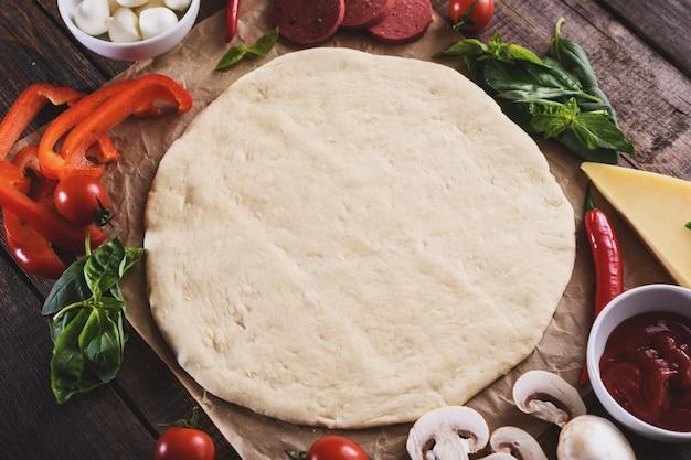 Vlak leg van ruw gerold pizzadeeg met ingrediënten op houten lijst