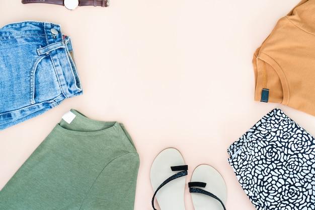 Vlak leg van vrouwenkleren en toebehoren die met schoenen, horloge worden geplaatst.