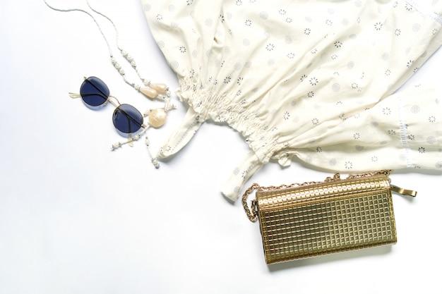Vlak leg van vrouwenkleren en toebehoren plaatste met glazen, handtas.