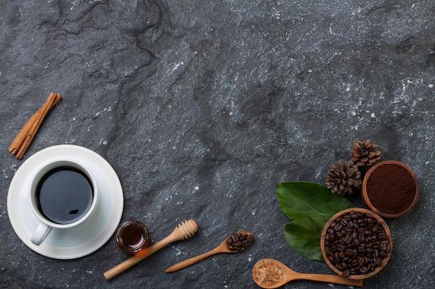 Vlak leg witte koffiekop, koffiebonen in houten kop op groen blad, suiker in houten lepel, pijnboom