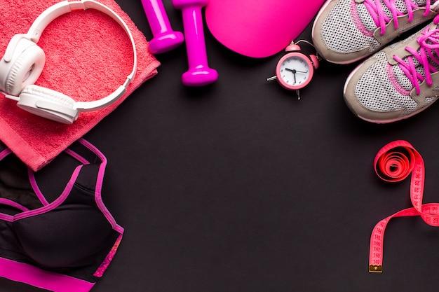 Vlak liggend frame met roze items en witte koptelefoons