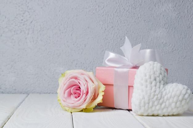 Vlakbij ligt een feestelijke achtergrond met een roos, een cadeau verpakt en een wit pluche hart.