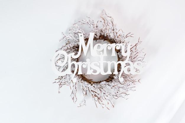 Vlakke brieven vrolijke kerstmis en krans van vorst met zonlichtstralen, leggen copyspace