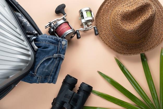 Vlakke grijze koffer met verrekijker, hoed, spijkerbroek, draaiend om te vissen en sandles. reis concept