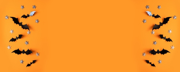 Vlakke halloween legt samenstelling van zwarte document knuppelsvliegen omhoog en gouden sterren op oranje oppervlakte