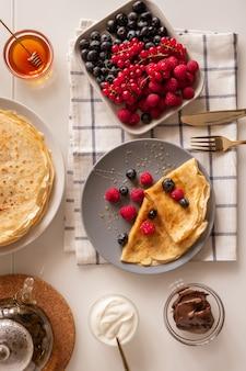 Vlakke indeling van keukentafel geserveerd voor het ontbijt met verse bessen, smakelijke pannenkoeken, zure room, honing en chocopasta