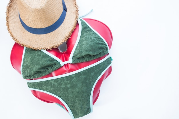 Vlakke lay-out van de zomer reis concept met hart draagt bikini op witte achtergrond, flat lay love vakantie