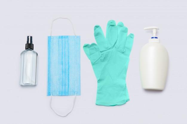 Vlakke lay-out van hygiënepunten - latex handschoenen, masker en handdesinfecterend middel op lichtgrijze achtergrond